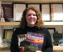 Appalachian alumnus Glenn Ramey '19 at the Explore Asheville Convention and Visitors Bureau, where she works as a group sales and service specialist. Ramey, who is pictured holding two visitor guides published by the bureau, graduated summa cum laude from Appalachian in 2019 with a B.A. in theatre arts and minors in general business and nonprofit management. Photo submitted