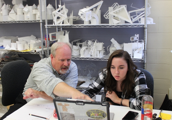 Alex Poorman works with a student