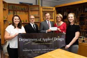 Dean Kloda receives a check from La-Z-Boy's Tim Solesbee