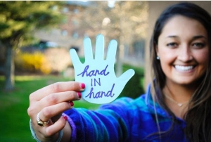 A student shares her blue paper hand cut-out